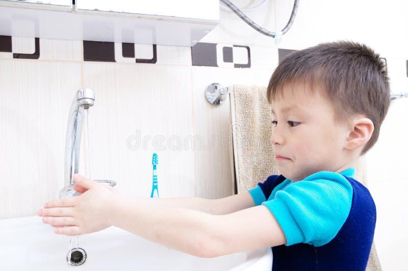 男孩洗涤的手,儿童个人医疗保健,卫生学概念,在面盆的孩子洗涤的手在卫生间里 免版税库存照片