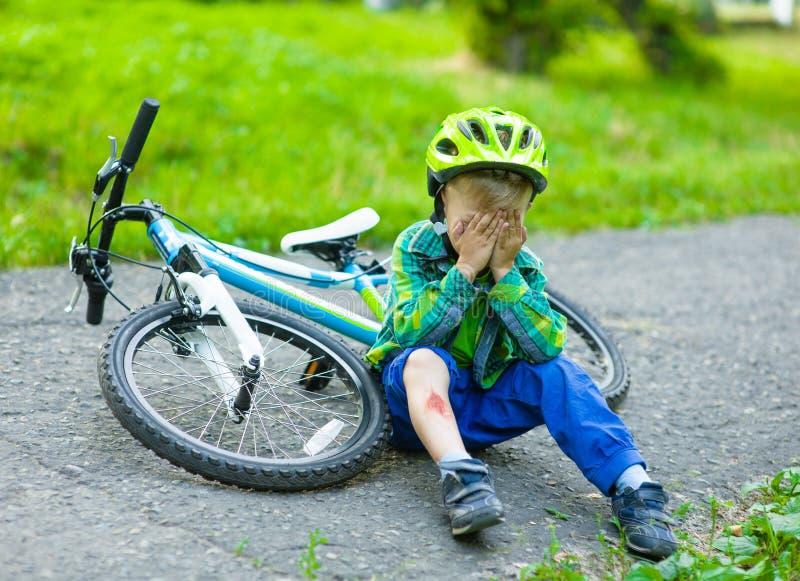 男孩从自行车跌倒了在公园 图库摄影