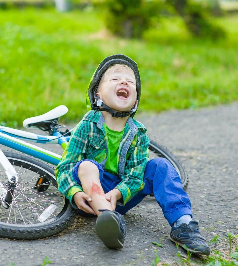 男孩从自行车跌倒了在公园 库存照片