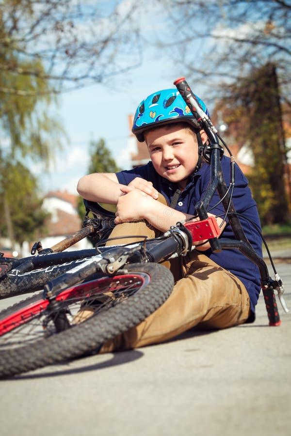 男孩从自行车跌倒了 免版税库存照片