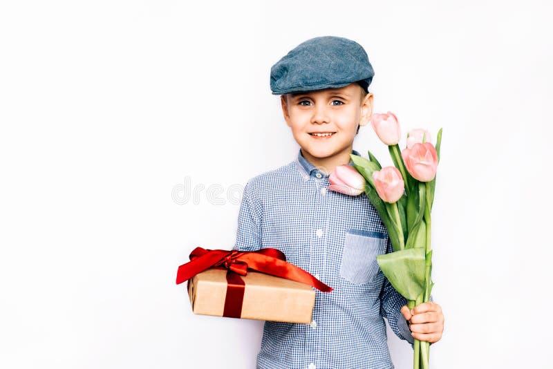 男孩给花和一件礼物 图库摄影
