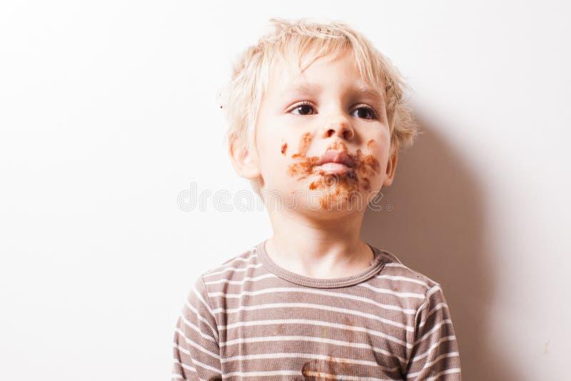 男孩eated巧克力,滑稽的肮脏的微笑的面孔 免版税图库摄影
