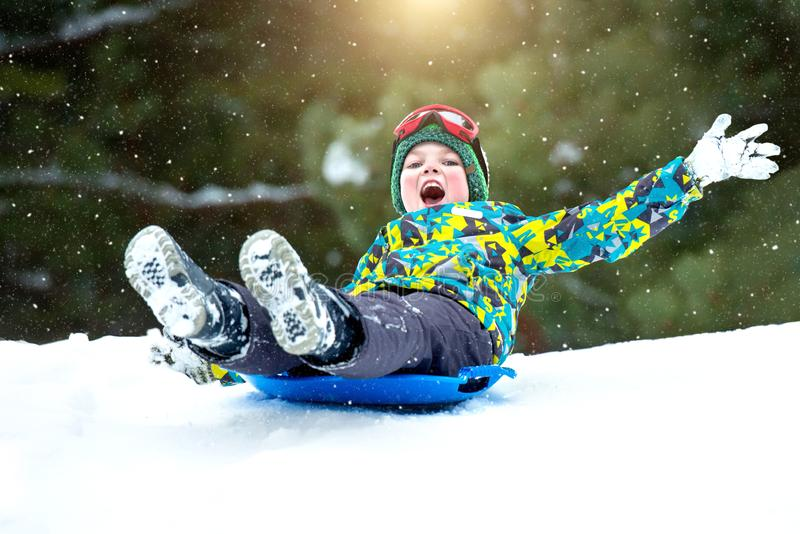 男孩sledding在多雪的森林室外冬天乐趣为圣诞节假期 库存照片