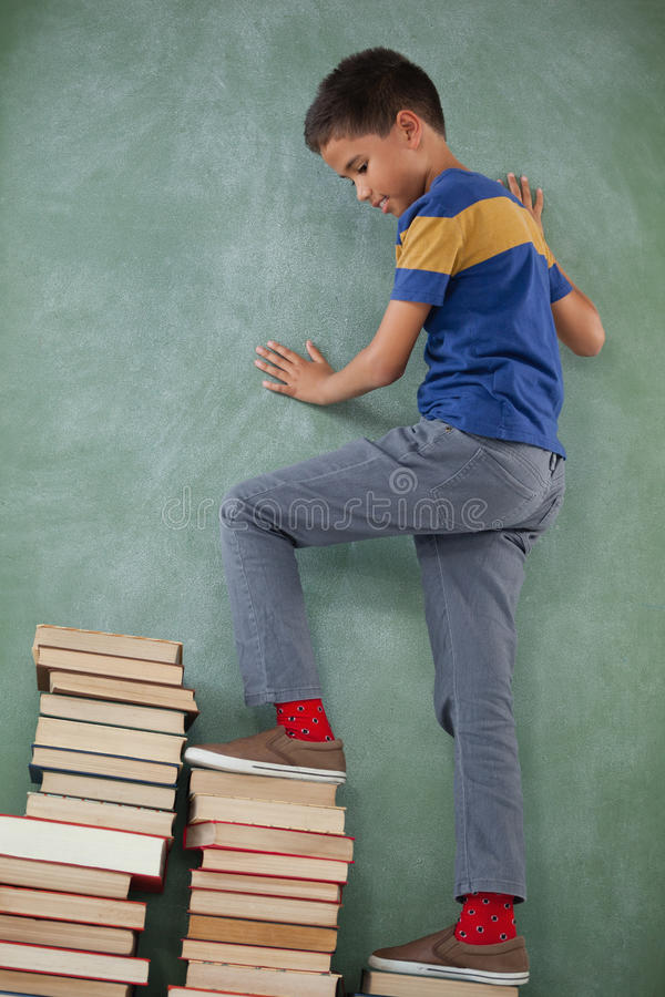 男小学生上升的步书架 库存图片