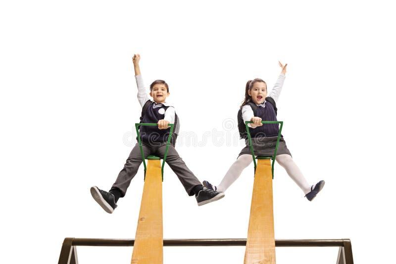 男小学生和女小学生使用在跷跷板的制服的 库存图片