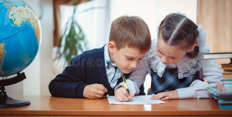 男小学生和女小学生有地球的 免版税库存图片