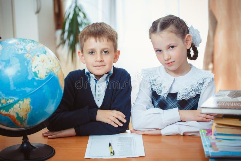 男小学生和女小学生有地球的 免版税库存照片