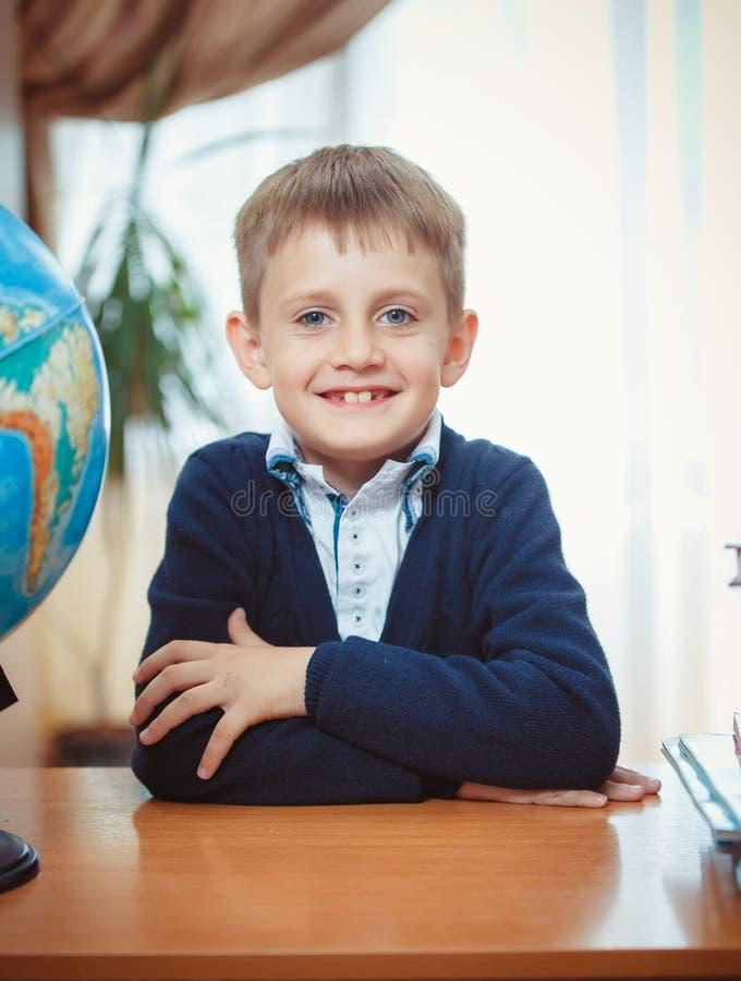 男小学生坐在书桌 库存照片