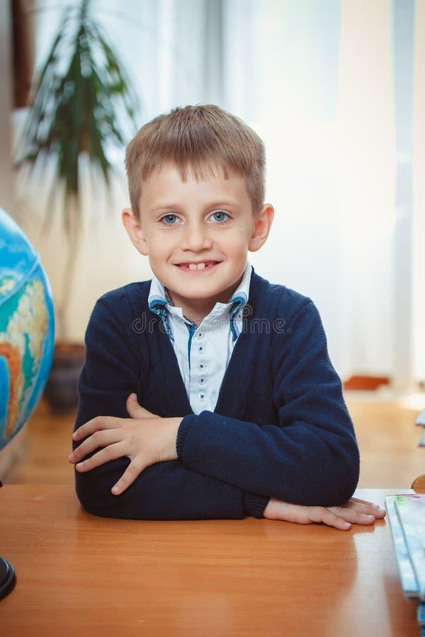 男小学生坐在书桌 库存图片