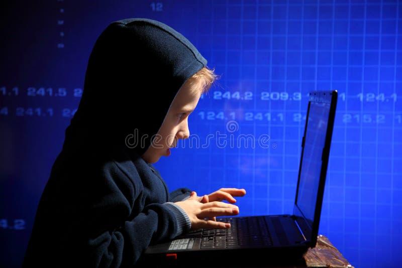 年轻男小学生奇迹-黑客 黑客在工作 免版税库存照片