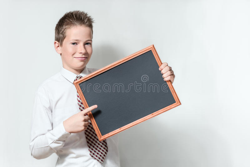 男小学生指出干净的黑黑板 库存图片