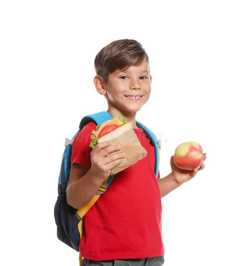 男小学生用健康食物和背包 免版税库存图片