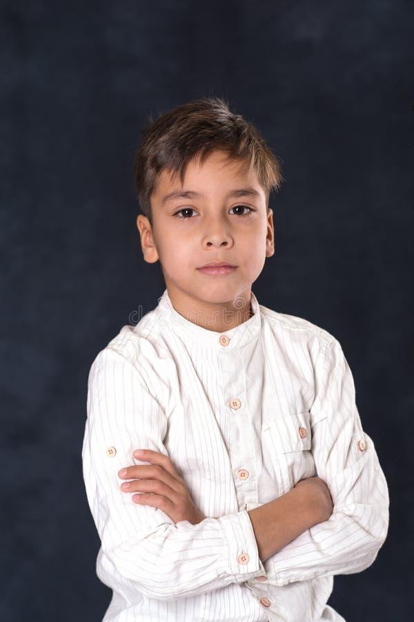 男小学生的画象一件白色衬衣的. 严重, 发型.图片