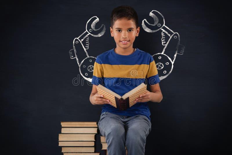 男小学生的综合图象坐堆书 免版税库存照片