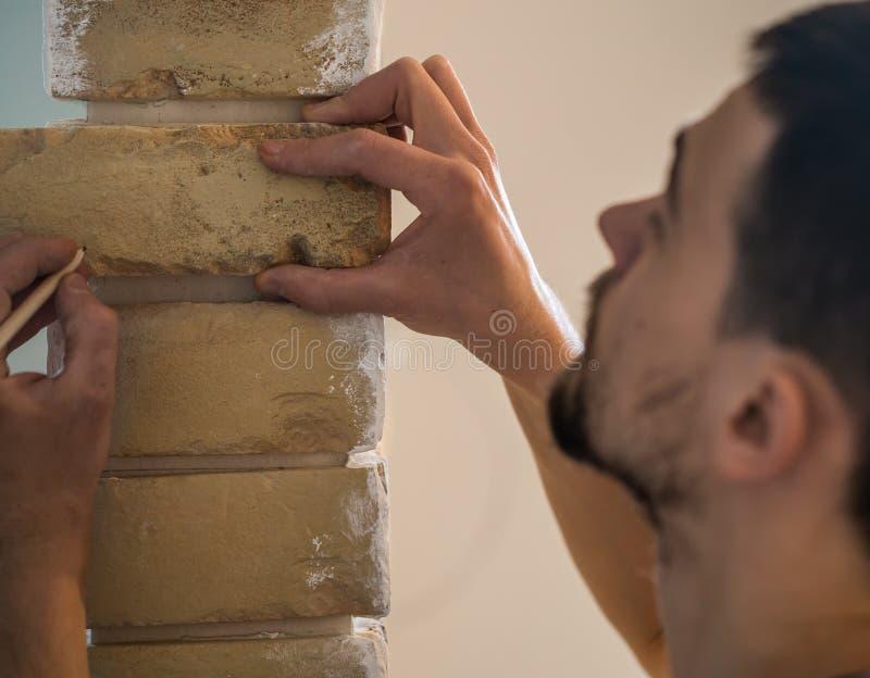 男性与有厘米的砖墙一起使用 免版税库存图片