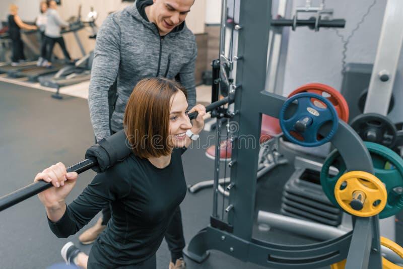 男性个人要做在健身房的锻炼的健身教练员帮助的年轻女人 体育、运动员、训练、健康生活方式和人们 免版税库存照片