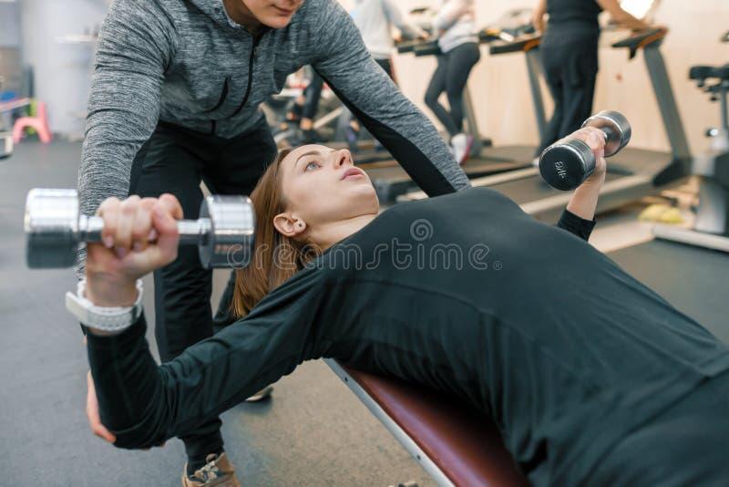 男性个人要做在健身房的锻炼的健身教练员帮助的年轻女人 体育、运动员、训练、健康生活方式和人们 库存照片