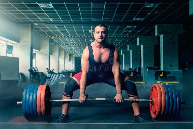 男性举重运动员准备拉扯重的杠铃 免版税库存照片