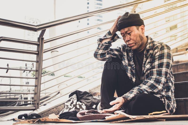男性从人类善良本性的叫化子等待的金钱,无家可归者在城市 免版税库存照片