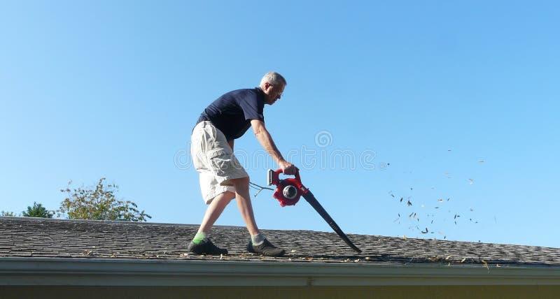 男性从天沟的房主吹的叶子 免版税库存照片