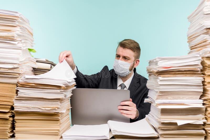 男性会计师或公司经理在大流行病的办公室工作,因为积累的纸张工作 保护性医疗 免版税图库摄影