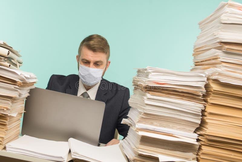 男性会计师或公司经理在大流行病的办公室工作,因为积累的纸张工作 保护性医疗 库存图片