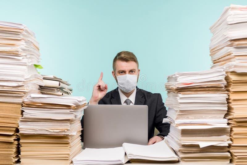 男性会计师或公司经理在大流行病的办公室工作,因为积累的纸张工作 保护性医疗 免版税库存图片
