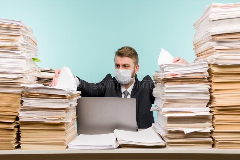 男性会计师或公司经理在大流行病的办公室工作,因为积累的纸张工作 保护性医疗 免版税库存照片