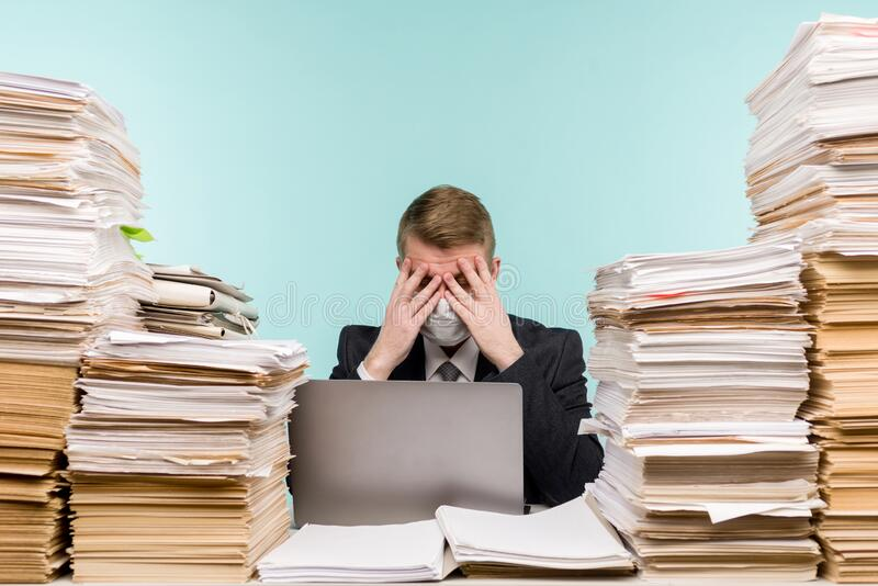 男性会计师或公司经理在大流行病的办公室工作,因为积累的纸张工作 保护性医疗 库存照片