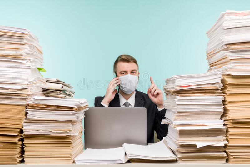 男性会计师或公司经理在大流行病的办公室工作,因为积累的纸张工作 保护性医疗 图库摄影