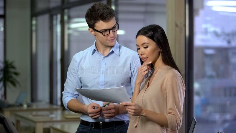 男性会计谈论费用与显示纸的公司的女性主任 免版税库存照片