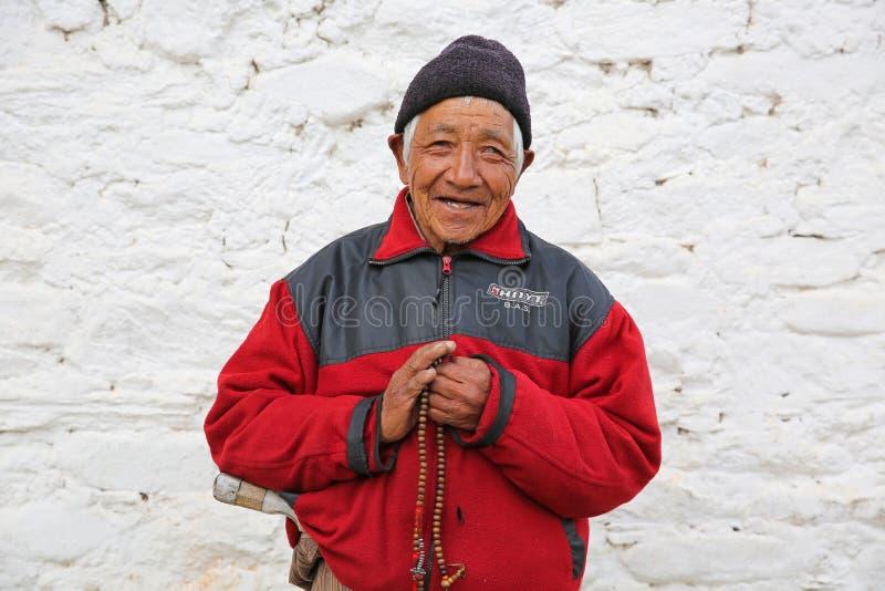 男性佛教香客抓住在寺庙,不丹的念珠 免版税库存照片