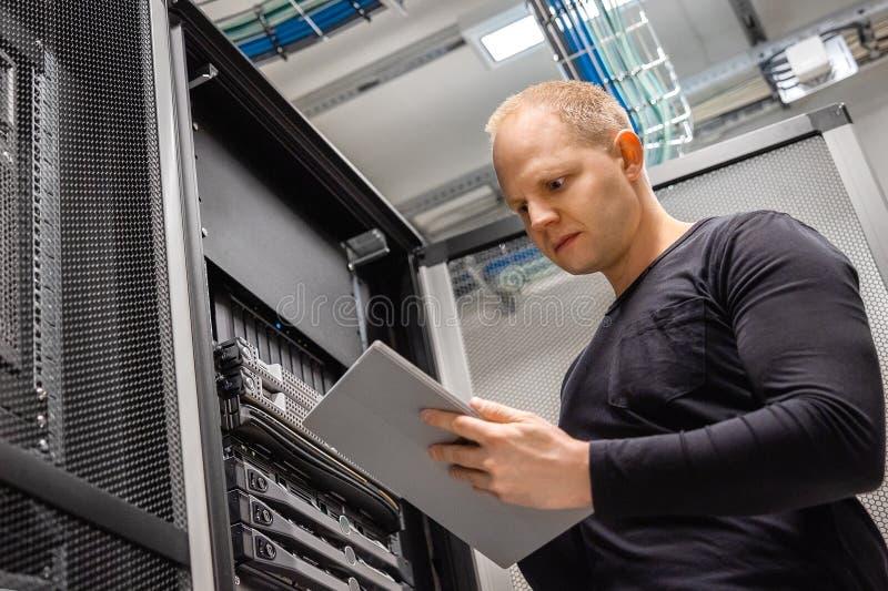 男性使用监测数字的片剂的资讯科技专业Datacenter状态 图库摄影