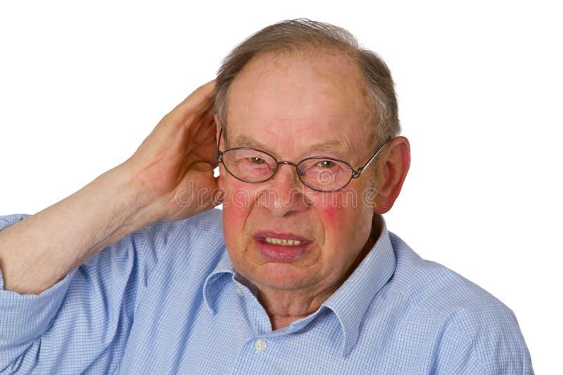男性前辈用在耳朵的现有量 免版税库存照片
