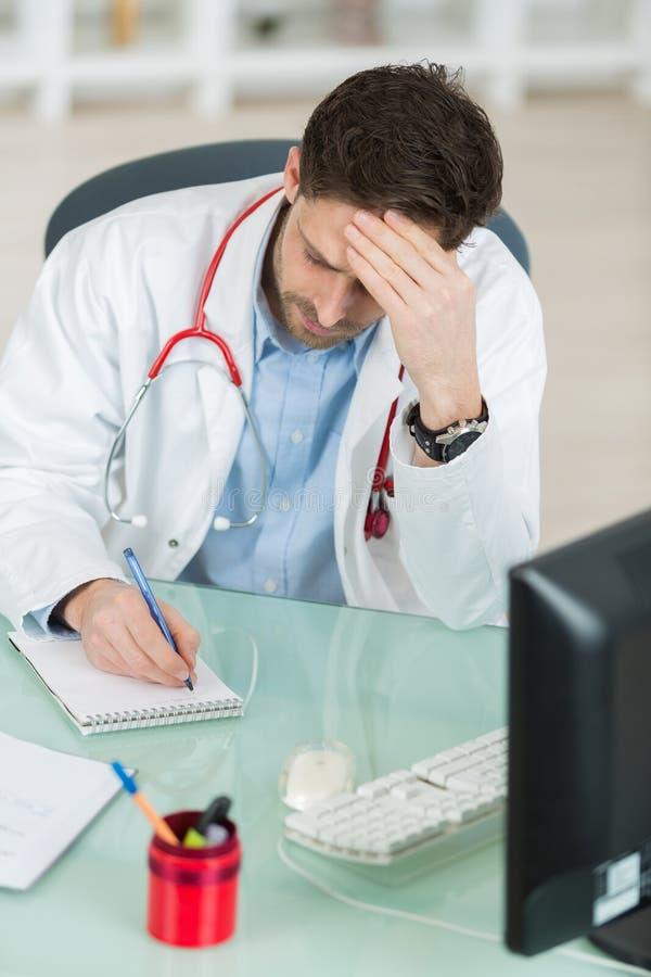 男性医生似乎疲乏或沮丧在工作 免版税库存照片