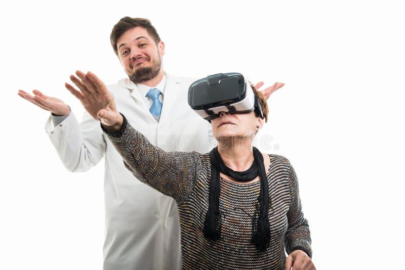 男性医生和女性资深病人有vr风镜打手势 免版税库存照片