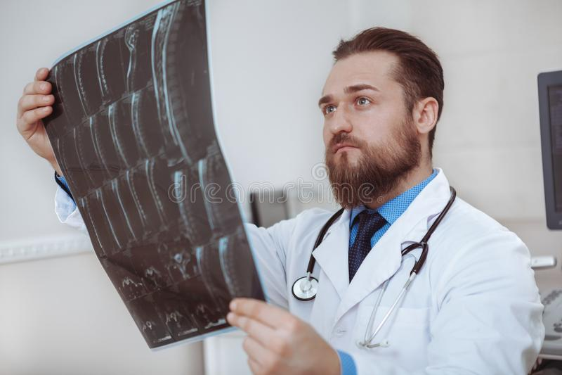 男性医生审查的X-射线扫描在他的办公室 免版税库存照片