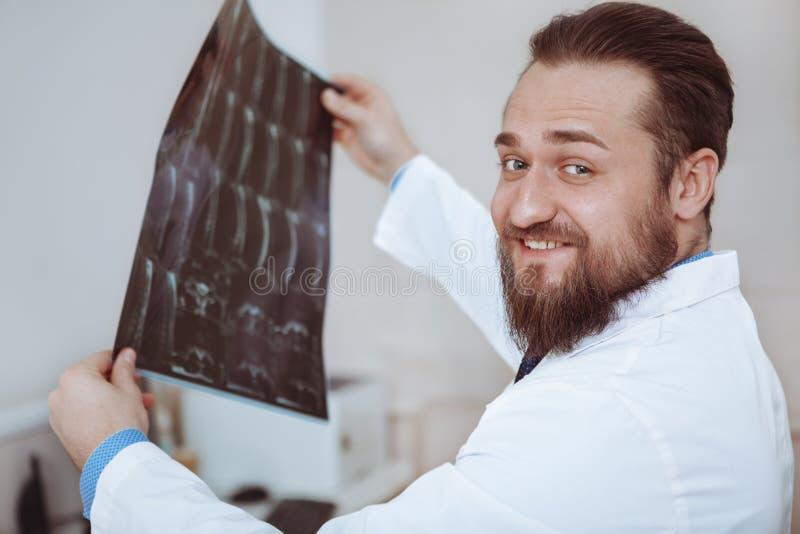 男性医生审查的X-射线扫描在他的办公室 库存照片