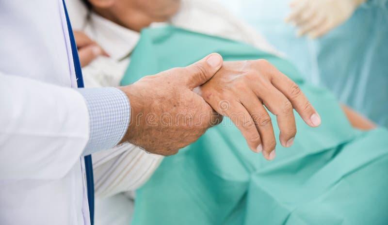 男性医生检查老人患者脉冲 免版税库存照片