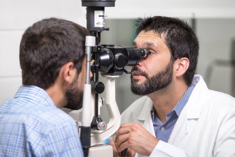 男性医生眼科医生检查英俊的年轻人眼睛视觉现代诊所的 医生和患者 库存图片
