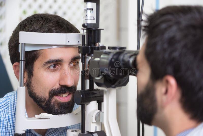 男性医生眼科医生检查英俊的年轻人眼睛视觉现代诊所的 医生和患者 免版税库存图片