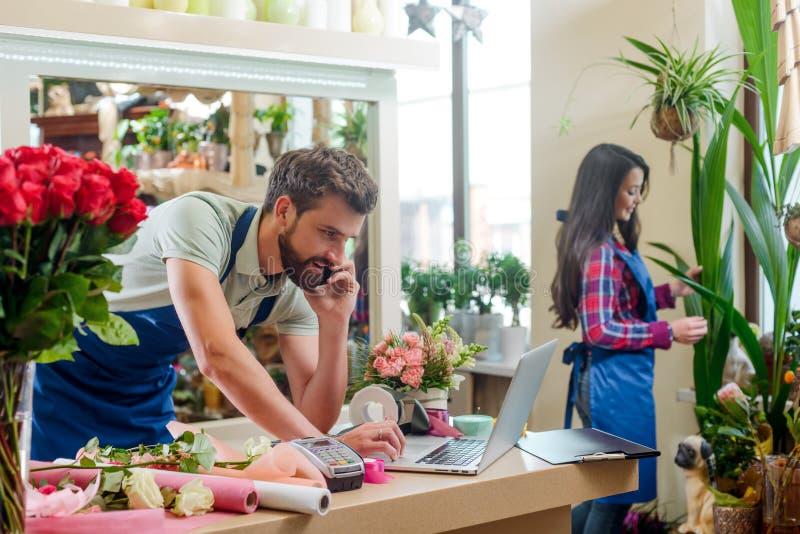 男性卖花人谈话与客户 库存照片