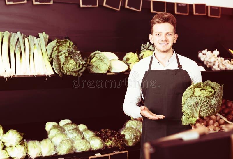 年轻男性卖主提供的圆白菜 库存图片