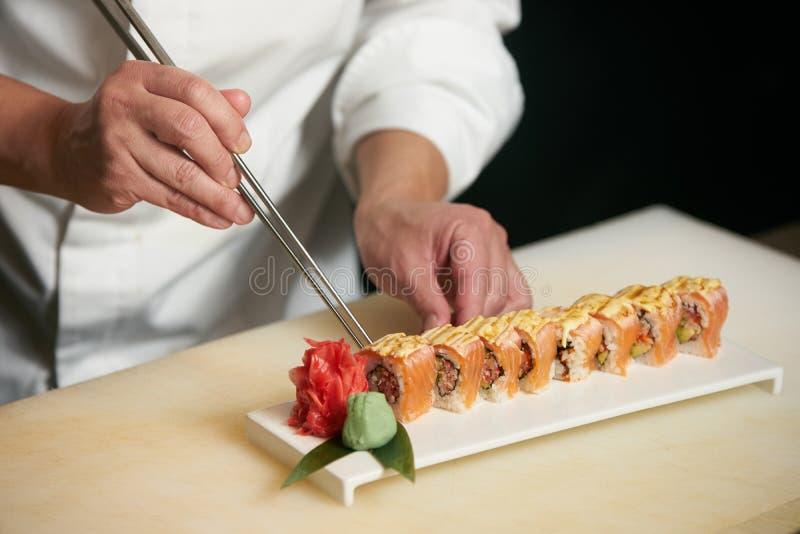 男性厨师在餐馆厨房里烹调准备寿司 免版税图库摄影