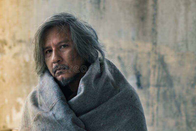 男性叫化子,无家可归的人有毯子的在走道街道上在城市等待的仁慈人民给金钱或食物 免版税库存照片