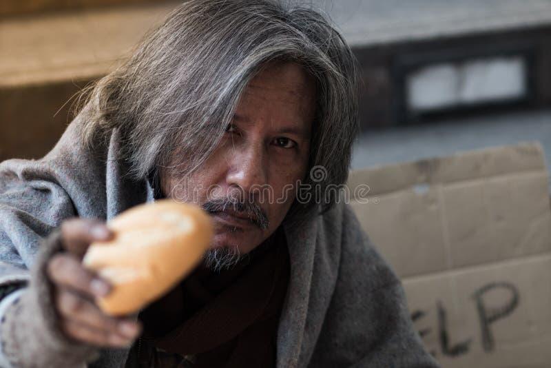 男性叫化子,给面包或食物做饥饿的无家可归的人有愉快的面孔 免版税库存图片