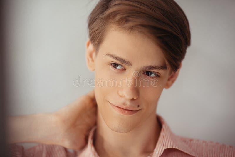 男性可爱的欧洲年轻人特写镜头画象有棕色眼睛的,微笑 在一个脖子的手,反对空白 免版税库存照片