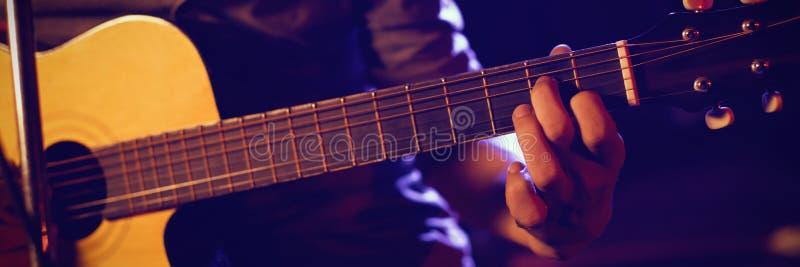 男性吉他弹奏者的中间部分音乐音乐会的 库存图片