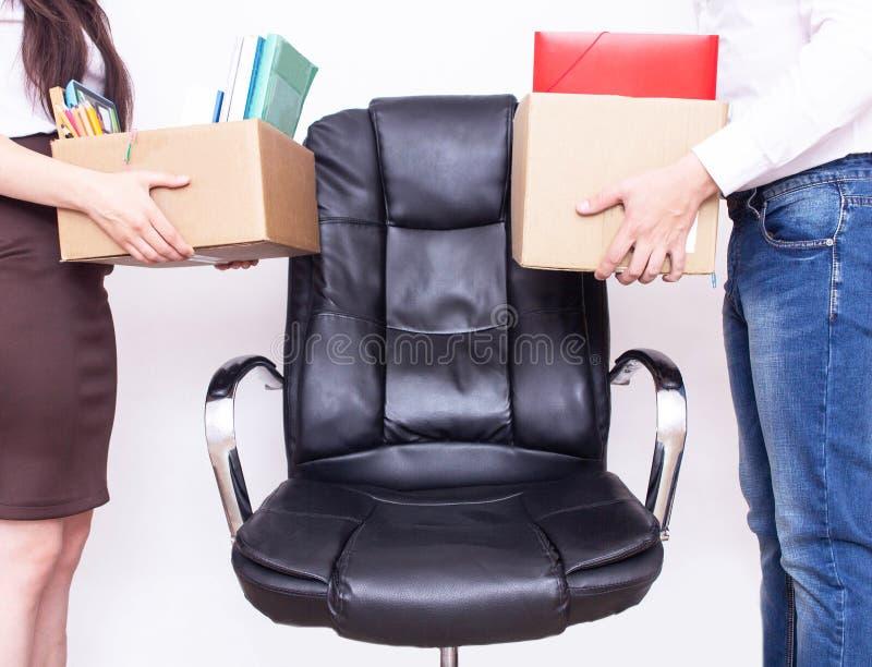 男性和女孩办公室工作者站立与他们的竞争和失业的同一个工作场所概念的私人物品 库存图片