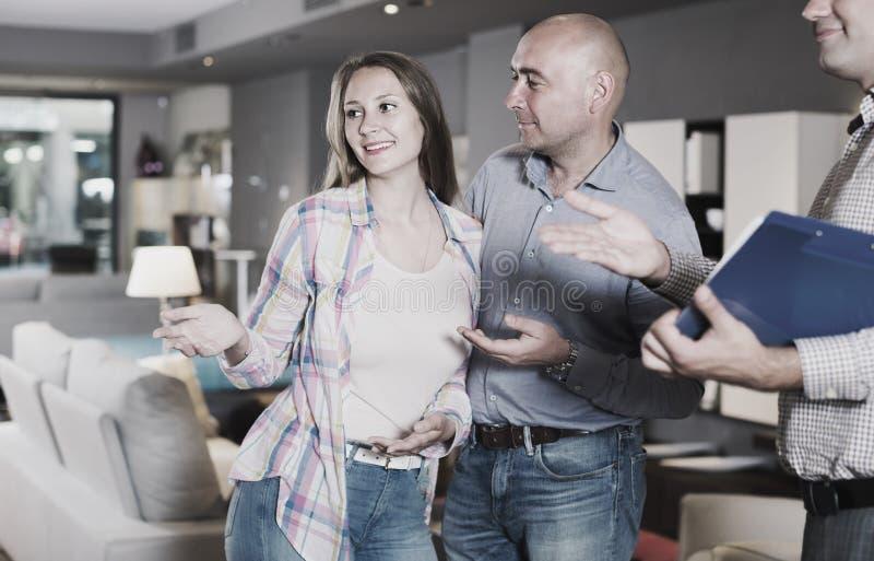 男性和女性与卖主协商选择新的沙发 免版税图库摄影